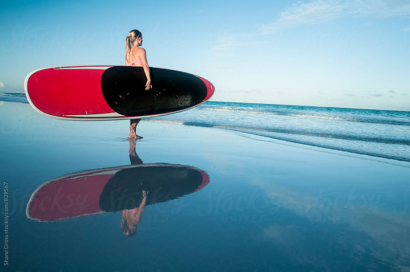 Girl Holding Stand Up Paddle Board on Beach by Shane Gross for Stocksy United