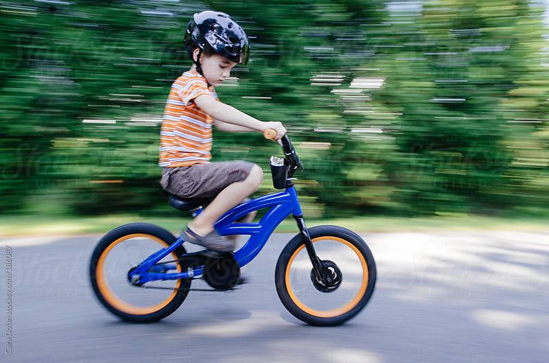 Boy riding his bike by Cara Dolan for Stocksy United