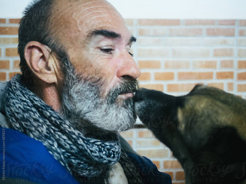 Old homeless kissing his dog by Martin Matej for Stocksy United