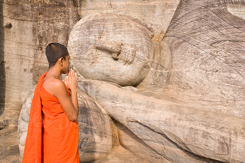Monk praying at a rock-cut image of the Buddha in the Gal Vihara, Polonnaruwa (Polonnaruva), UNESCO World Heritage Site, Sri Lanka, Asia by Gavin Hellier for Stocksy United