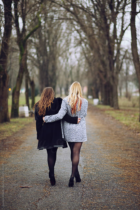 Two female friends walking in park by Jovana Rikalo for Stocksy United