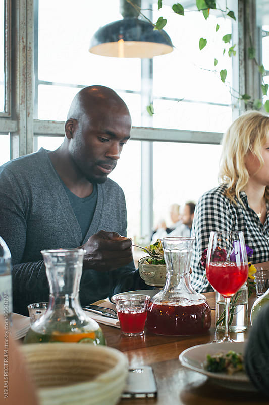 Portrait of Black Man Helping Himself to Food in Bright Restaurant by VISUALSPECTRUM for Stocksy United