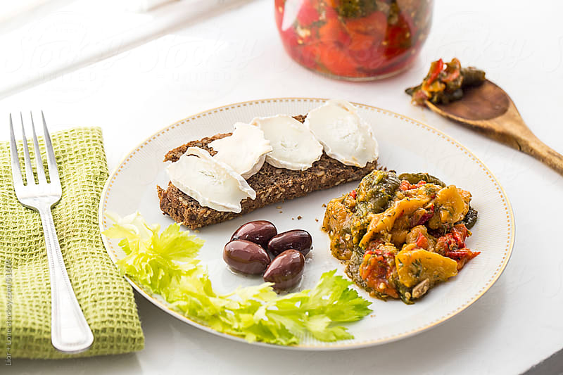 Lunch with goat cheese, rye bread and roasted peppers on vintage by Lior + Lone for Stocksy United