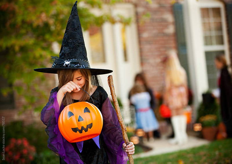 Halloween: Girl Looking Into Candy Bucket by Sean Locke for Stocksy United