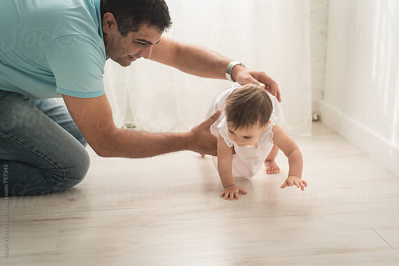 A Father Grabs His Young Daughter As She Crawls by Alison Winterroth for Stocksy United