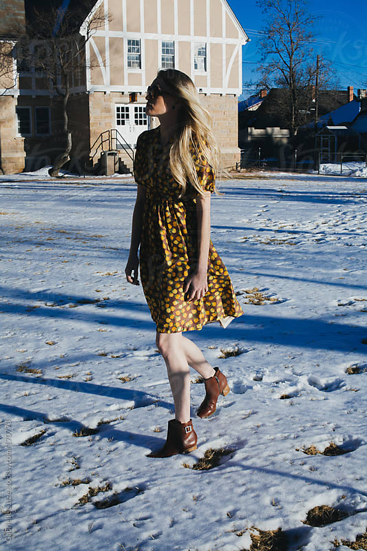Beautiful Girl in Vintage Dress Walking Through Snow by Gabrielle Lutze for Stocksy United