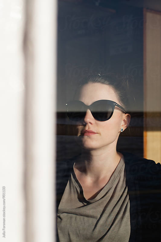 A beautiful young woman wearing sunglasses seen through a window. by Julia Forsman for Stocksy United