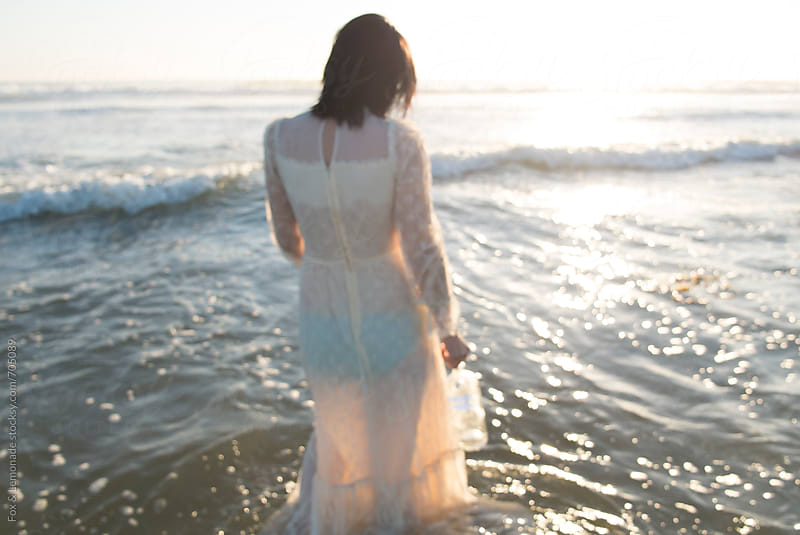 sad lady in wedding dress in the ocean water by Fox & Lemonade for Stocksy United