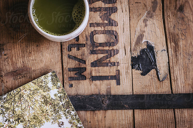 A Mug of Matcha placed on a Worn Wooden Board by Claudia Lommel for Stocksy United