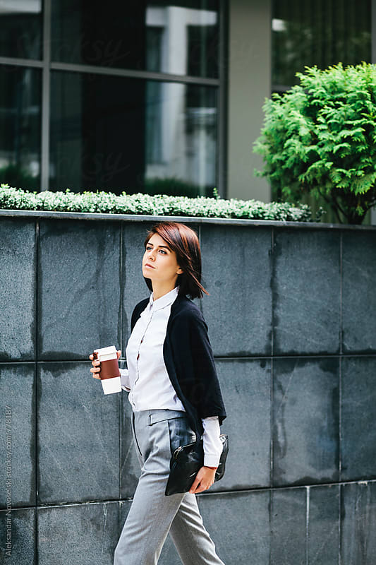 Young business woman walking on the street with coffe in her hands by Aleksandar Novoselski for Stocksy United