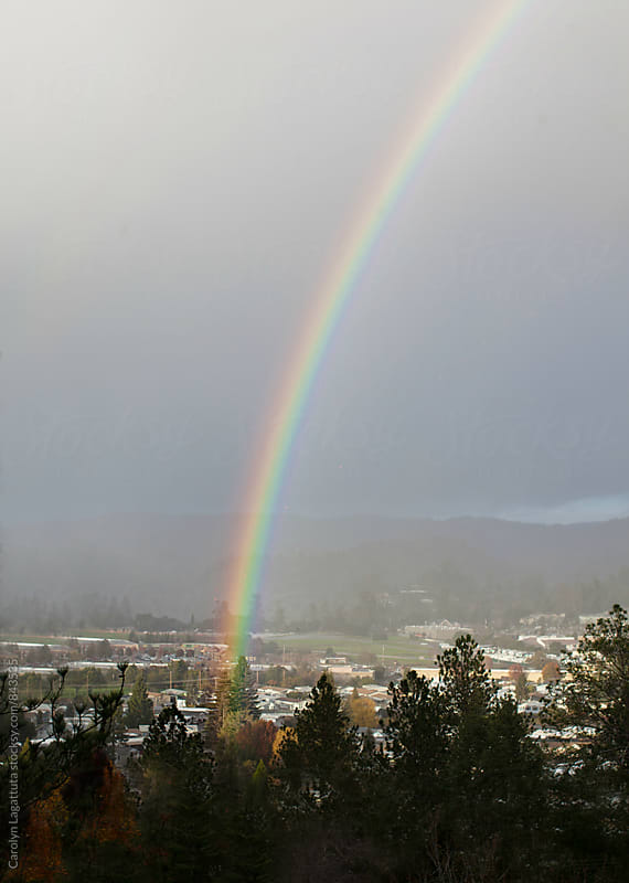 Bright rainbow in a valley on a rainy day by Carolyn Lagattuta for Stocksy United
