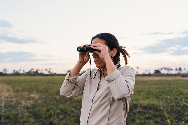 Woman animal watching in binoculars on African safari by Trent Lanz for Stocksy United