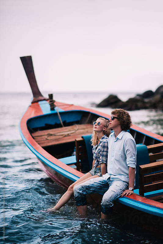 romantic couple sitting on boat  looking out to sea by Alexander Grabchilev for Stocksy United