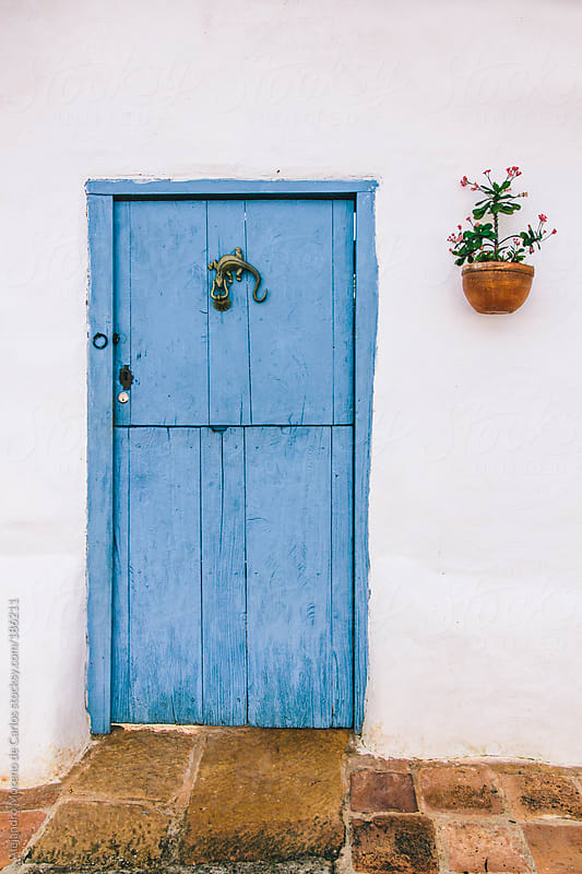 Blue door with lizard knocker against a white wall on a traditional patio in Barichara, Colombia by Alejandro Moreno de Carlos for Stocksy United