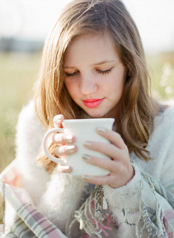Girl feeling the warmth from a cup of hot chocolate or coffee by Marta Locklear for Stocksy United