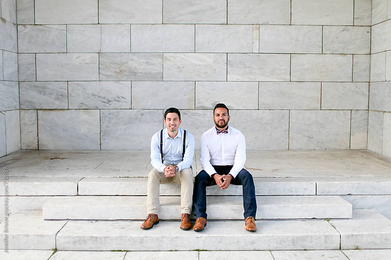 Two men sit in front of white marble wall by Jen Brister for Stocksy United