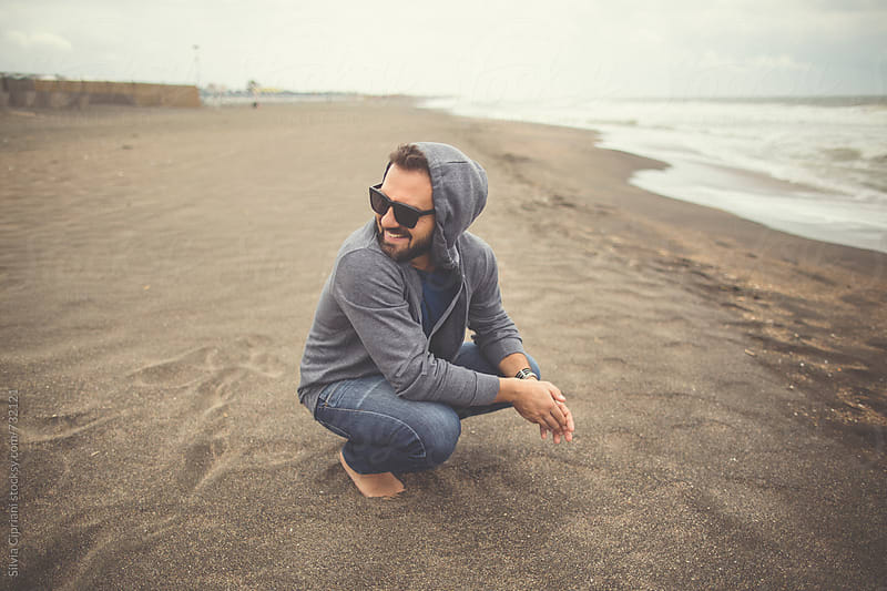 A man smiling on the beach in a windy day by Silvia Cipriani for Stocksy United
