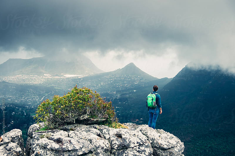 Female hiker on a rocky outcrop looking at stormy mountain view by Micky Wiswedel for Stocksy United