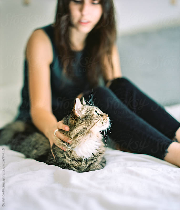 Girl petting cat on bed by Daniel Kim Photography for Stocksy United