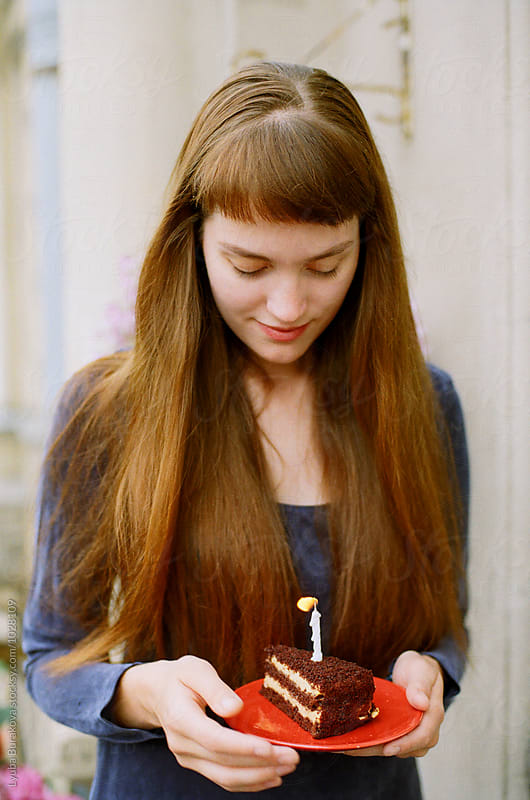 Young woman holding a plate with birthday cake by Liubov Burakova for Stocksy United