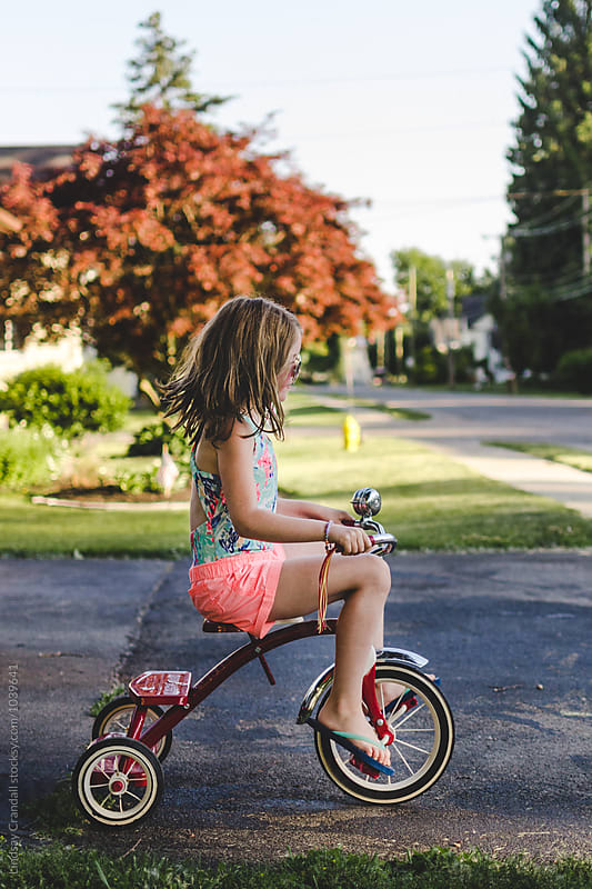 Happy child riding tricycle in summertime by Lindsay Crandall for Stocksy United
