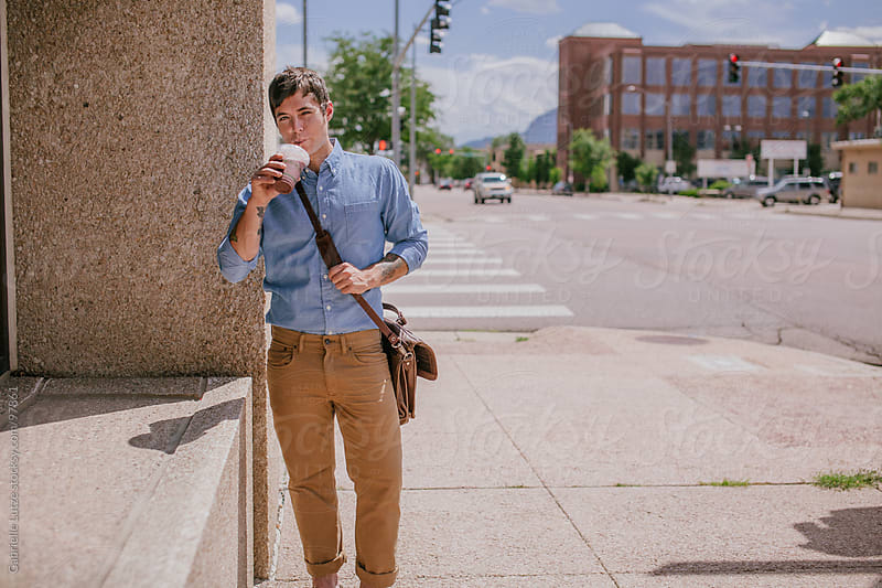 Man in business attire drinking a smoothie by Gabrielle Lutze for Stocksy United