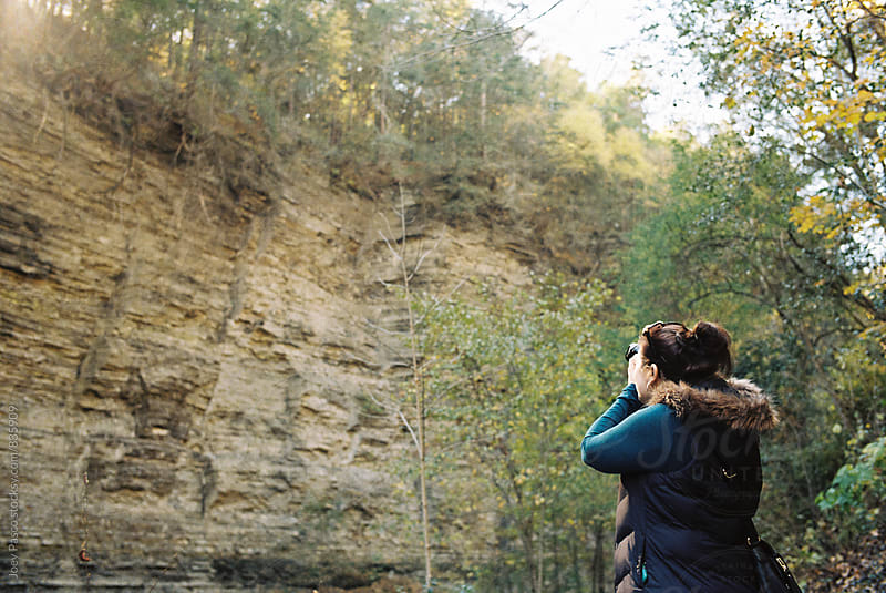 Woman with camera taking pictures outdoors in a gorge by Joey Pasco for Stocksy United