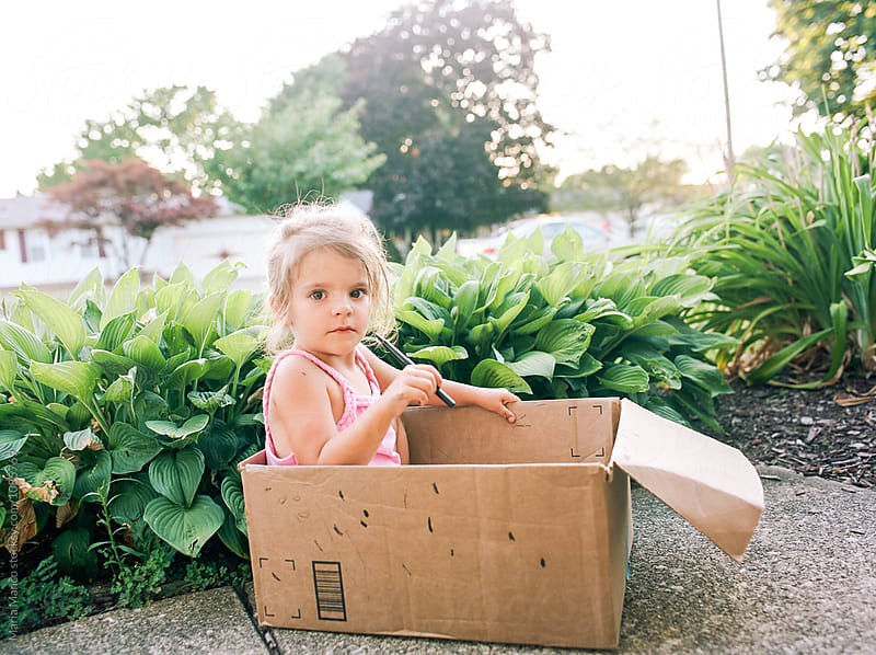 little girl sits in cardboard box by Maria Manco for Stocksy United