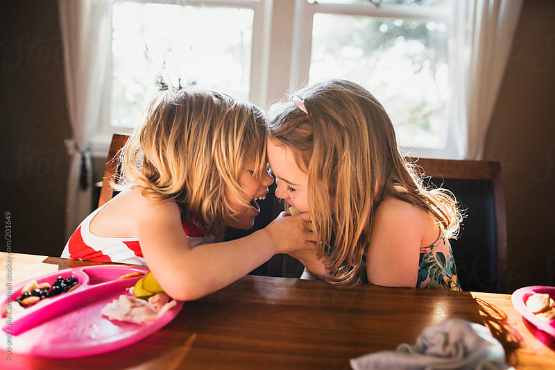 Two cute, young sisters being goofy - sharing cheese - at the lunch table by Rob and Julia Campbell for Stocksy United