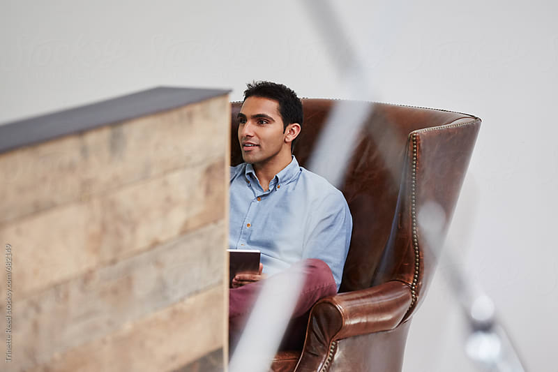 Millennial East Indian businessman in waiting area at office by Trinette Reed for Stocksy United