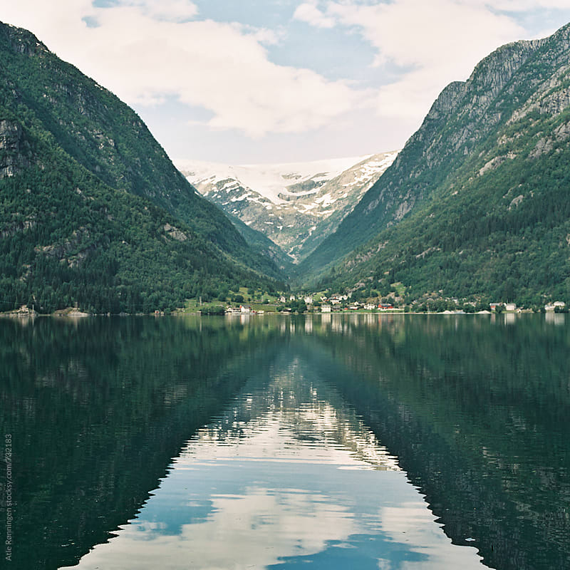 View to the mountain tops with reflection on the Norwegian fjords by Atle Rønningen for Stocksy United