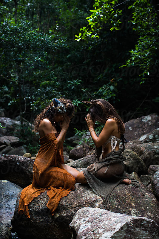 Two Women Praying in the Jungle by Mosuno for Stocksy United