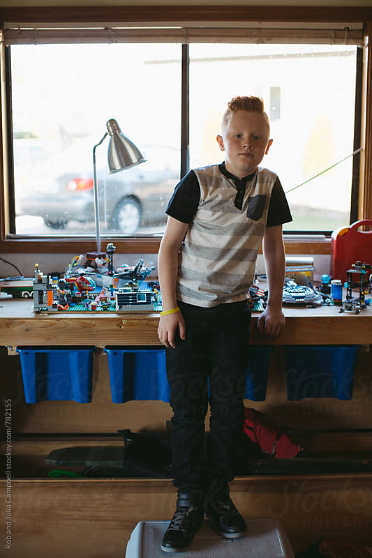 Serious, boy standing in front of building block work station by Rob and Julia Campbell for Stocksy United