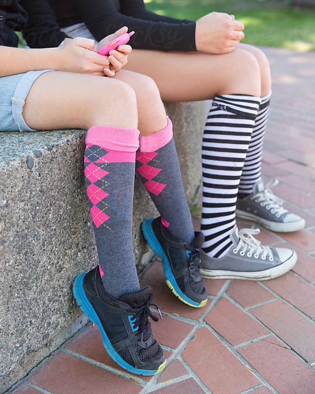 two tweens wearing colorful socks by Tanya Constantine for Stocksy United
