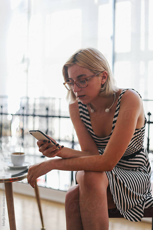 Woman in a coffee shop browsing on her mobile phone by Marija Kovac for Stocksy United