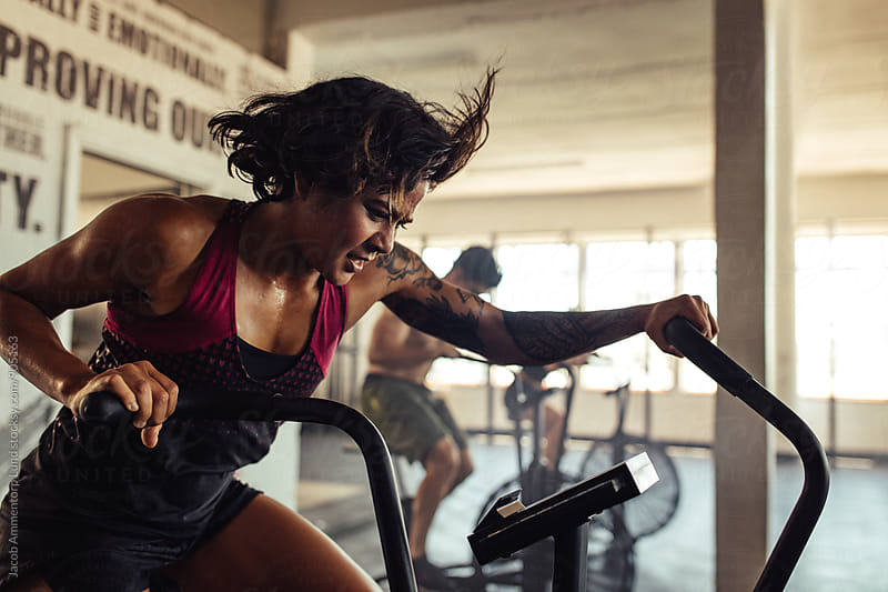 Fit young woman doing cardio workout at gym by Jacob Lund for Stocksy United