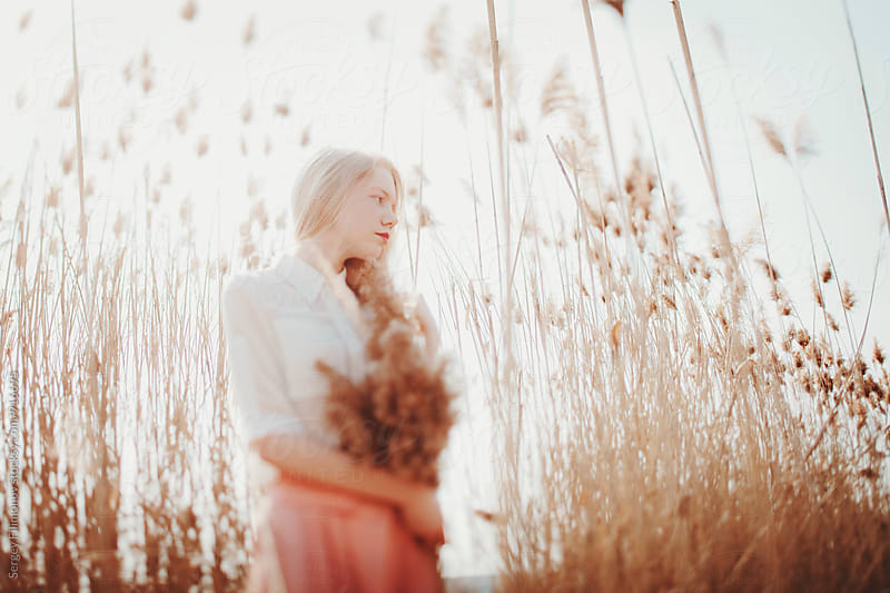 Portrait of a young blonde girl against the sky in a field by Sergey Filimonov for Stocksy United
