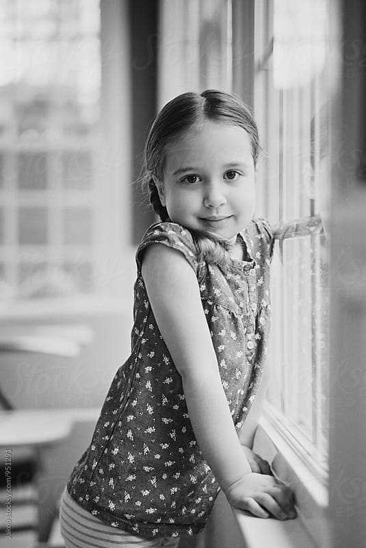 Black and white portrait of a cute young girl in pigtails looking at camera by Jakob for Stocksy United