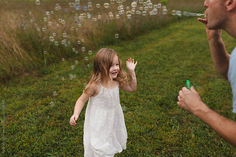 Dad blows bubbles for daughter outdoors by Amanda Worrall for Stocksy United