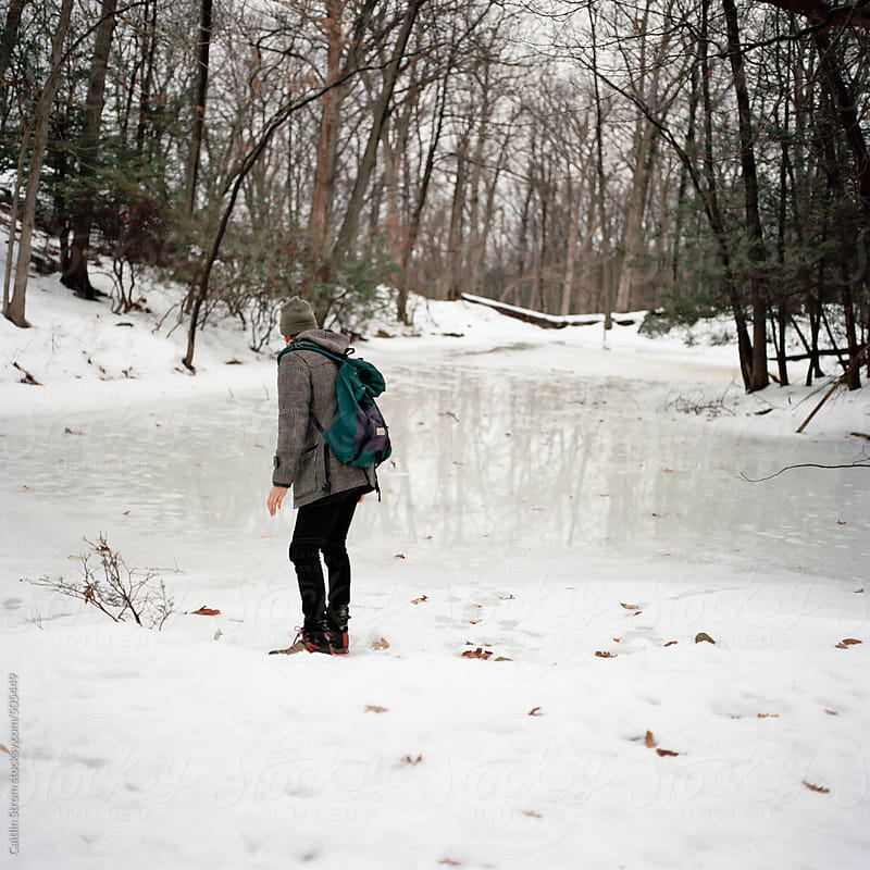 Young man on the edge of the ice by Caitlin Strom for Stocksy United