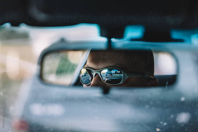 Car driver in mirrored sunglasses reflected in rearview mirror by Ilya for Stocksy United