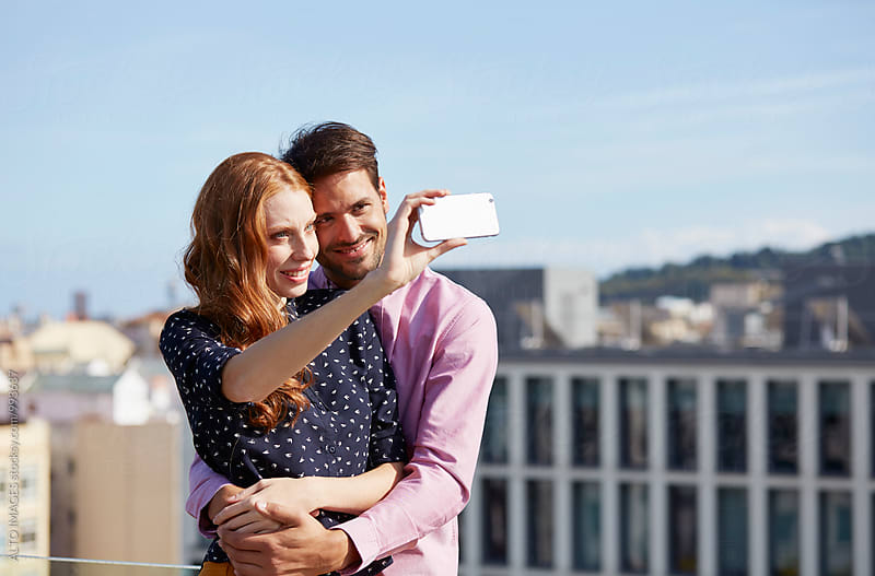 Couple Embracing While Talking Selfie In City by ALTO IMAGES for Stocksy United