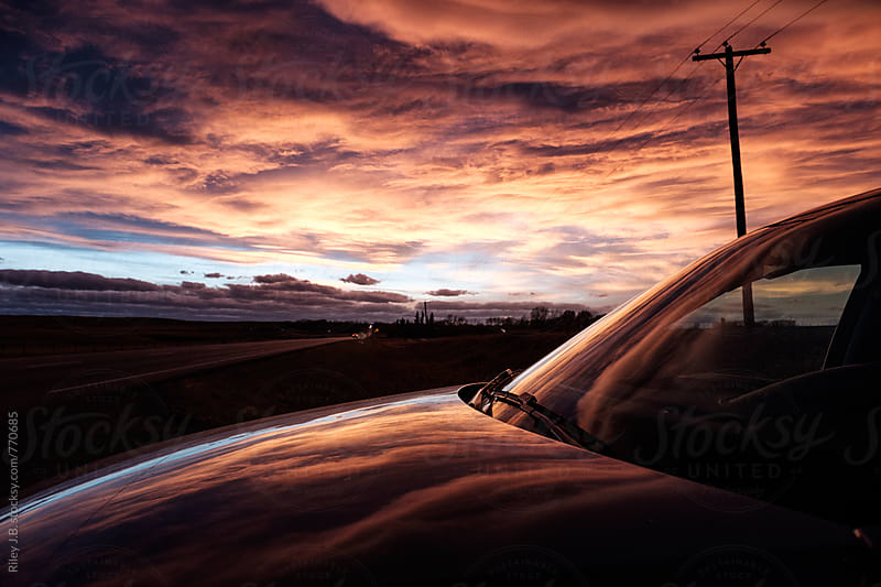 An impressive rural autumn sunset reflected on a vehicle by Riley J.B. for Stocksy United