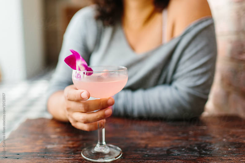 A woman drinking a pink cocktail with a flower in it.