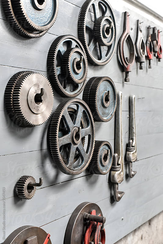 Gear wheels hanging on a wall of workshop by Bisual Studio for Stocksy United