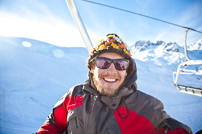 Young snowboarder smiling while sitting in a chairlift on a sunny day in the mountains by Ivo de Bruijn for Stocksy United