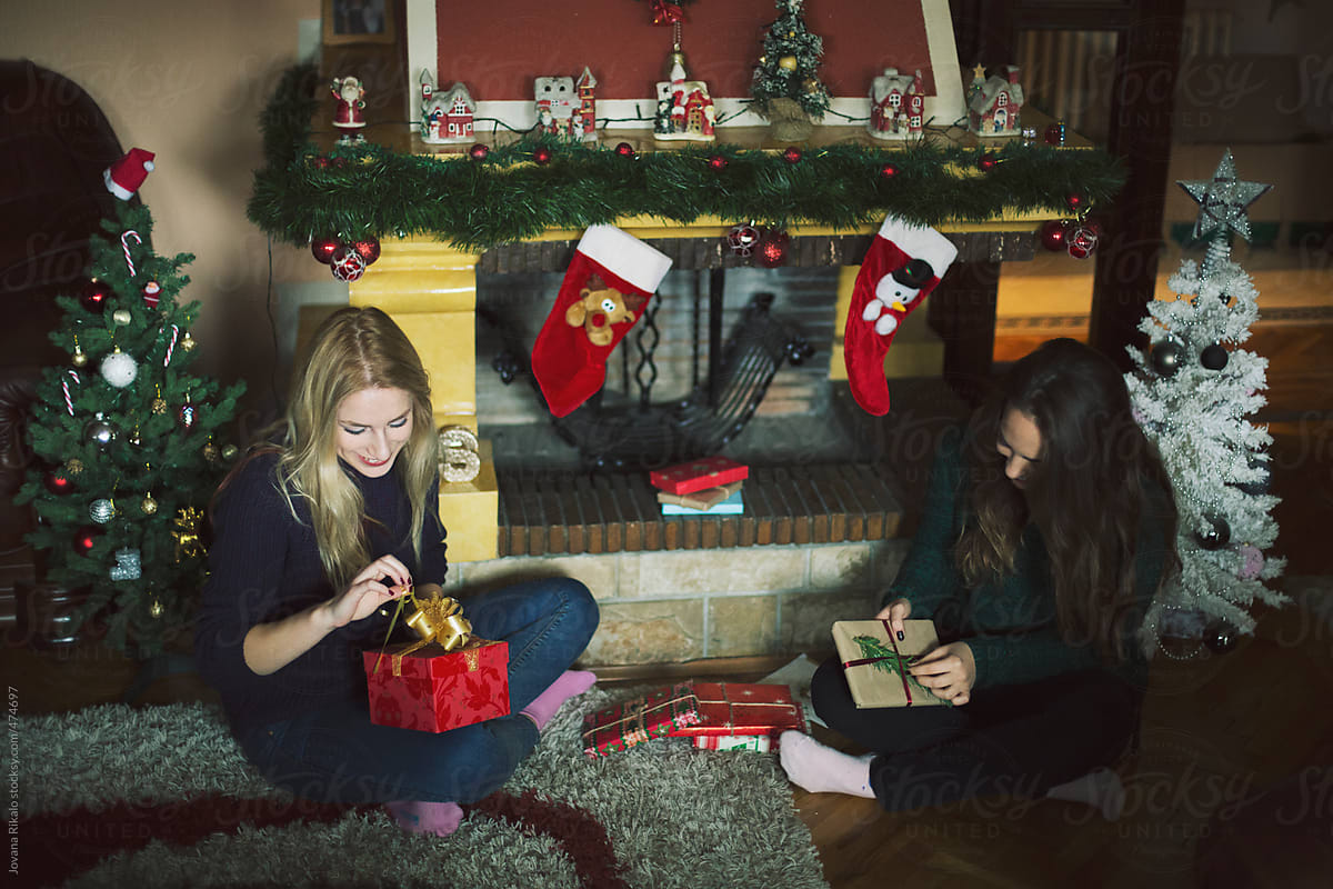 Two Female Friends Opening Christmas Gifts   Stocksy United