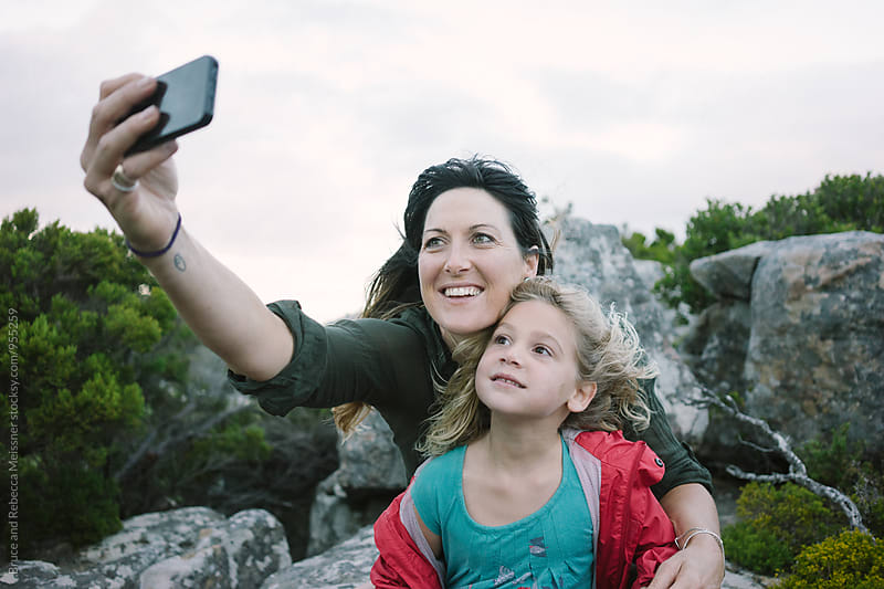 Mom and daughter selfie by Bruce and Rebecca Meissner for Stocksy United