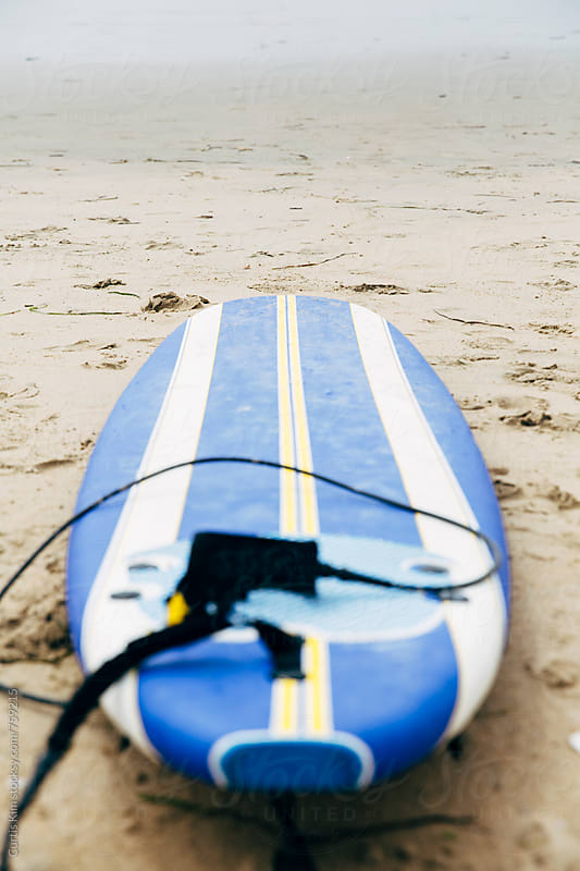 Surfboard on sand at the beach by Curtis Kim for Stocksy United