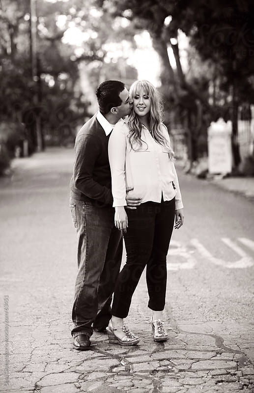 Mixed race couple standing in street while he kisses her with hands around her waist by Dina Giangregorio for Stocksy United